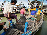 07 NOVEMBER 2014 - SITTWE, RAKHINE, MYANMAR: A Rohingya Muslim men climb into a boat in the port of a Rohingya IDP camp near Sittwe. The government of Myanmar has forced more than 140,000 Rohingya Muslims who used to live in Sittwe, Myanmar, into squalid Internal Displaced Person (IDP) camps. The forced relocation took place in 2012 after sectarian violence devastated Rohingya communities in Sittwe and left hundreds dead. None of the camps have electricity and some have been denied access to regular rations for nine months. Conditions for the Rohingya in the camps have fueled an exodus of Rohingya refugees to Malaysia and Thailand. Tens of thousands have put to sea in rickety boats hoping to land in Malaysia but sometimes landing in Thailand. The exodus has fueled the boat building boom on the waterfront near the camps. Authorities expect the pace of refugees fleeing Myanmar to accelerate during the cool season, December through February, when there are fewer storms in the Andaman Sea and Bay of Bengal.   PHOTO BY JACK KURTZ