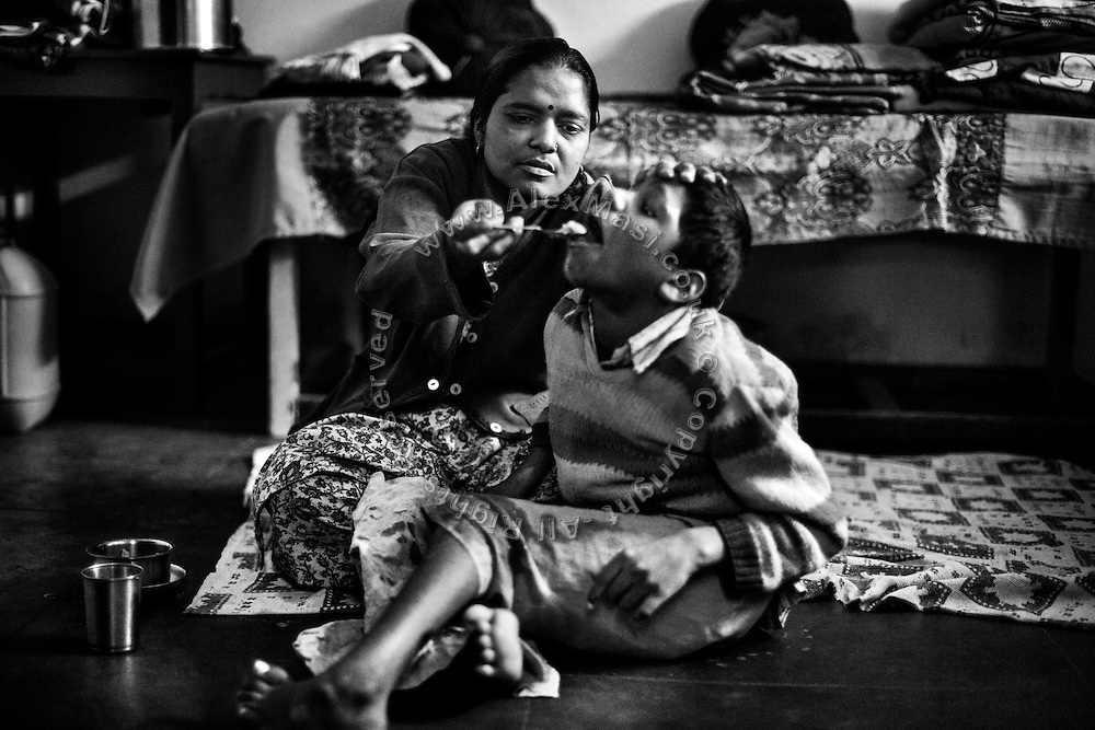 Siddhesh, 12, a boy affected by severe cerebral palsy, is being fed lentils and soup by his mother, Meeta, 33, while inside their home in Nariyal Kheda, Bhopal, Madhya Pradesh, central India. Siddhesh's father has abandoned them years ago. His mother, a '1984 Gas Survivor', is also suffering from a mild mental illness, and they now live with Siddhesh's maternal grandfather on the meagre pension he is earning after working as a civil servant.