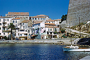 Historic buildings on waterfront in the coastal town of Calvi, Corsica, France in late 1950s