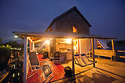 The porch of an old beach cottage is lit up at dusk