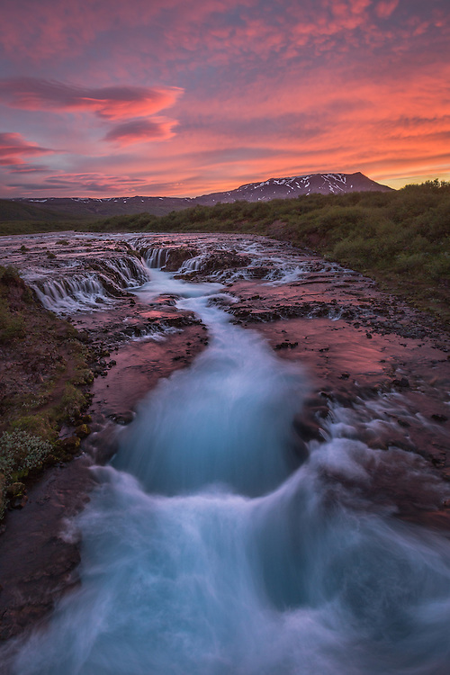 An icy glacial river flows over the waterfall Brúarfoss under a burning midnight sky.
