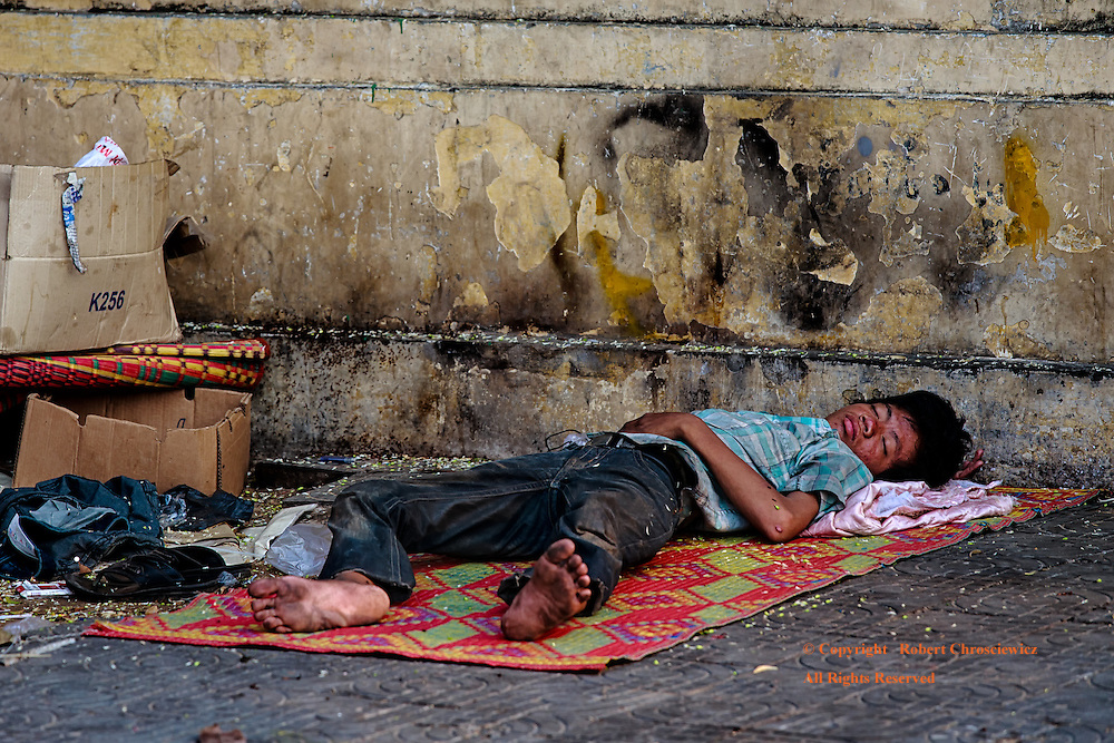 Sleep on the Street: A young man sleeps amongst the filth of the street, with only the thinnest of mats between himself and the concrete sidewalk, Phnom Penh Cambodia.