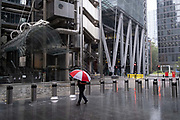 A male City worker carrying a red and white corporate brolly for 'EC3 Brokers', walks through a rain shower outside the lloyds of London building (left) on the corner of Lime Street and Leadenhall, during the Coronavirus pandemic - a time when the normal workforce is still working from home, on 17th August 2020, in London, England. (Richard Baker / In Pictures via Getty Images)
