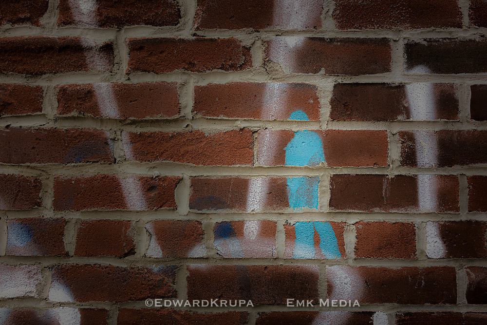 A brick wall with paint, and patched up mortar.