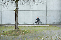 Young man riding bicycle against concrete wall, Munich, Bavaria, Germany