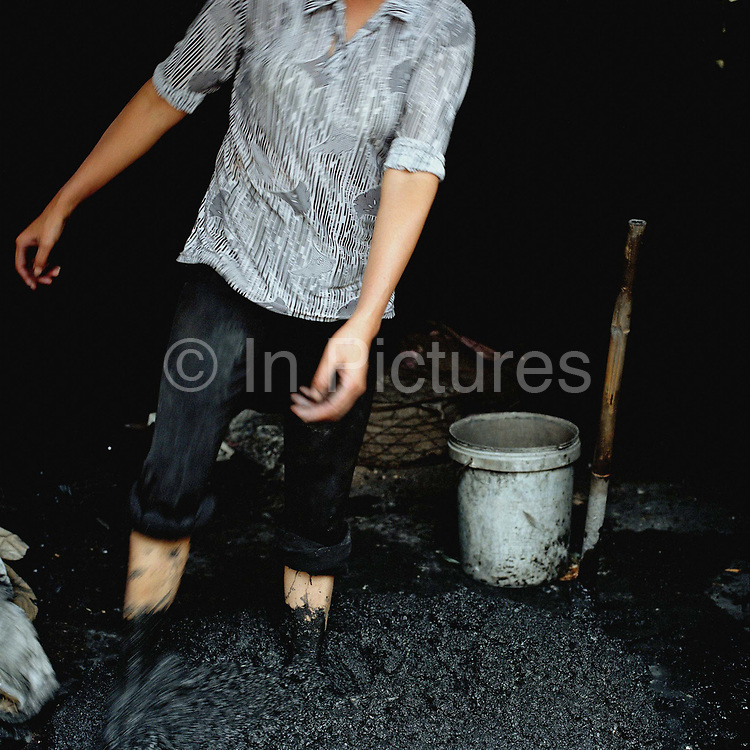 A worker mixing coal dust with her feet for making bricks for burning in the kilns, Bat Trang ceramic making village, Hanoi; Vietnam. With Vietnam's growing population making less land available for farmers to work, families unable to sustain themselves are turning to the creation of various products in rural areas.  These 'craft' villages specialise in a single product or activity, anything from palm leaf hats to incense sticks, or from noodle making to snake-catching. Some of these 'craft' villages date back hundreds of years, whilst others are a more recent response to enable rural farmers to earn much needed extra income.