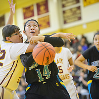 022715       Adron Gardner/Independent<br /> <br /> Tohatchi Cougar Shawntaya Murphy (32), left, reaches in on Navajo Prep Eagle Jazmin Benally (14) during the district 1AAA championship in Tohatchi Friday.