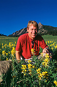 Mo Siegel by the FlatIrons mountains in Boulder, Colorado picking flowers that can be used in tea.  He was the founder of Celestial Seasonings.