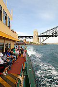 Passengers on board Sydney Harbour Ferry, with Sydney Harbour Bridge in background