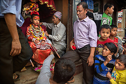 Unika Vajracharya sits on her throne in a shop in Lagankhel, as an attendant adjusts a silver necklace believed to imbue her with godly power. The newly selected Kumari of Patan's first official role is to witness the ritual bathing of the image of a rain god.