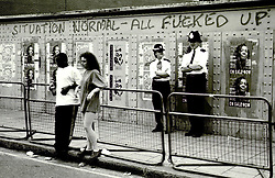 1989. Notting Hill, London, England. .'Situation Normal - All Fucked Up.' Graffiti daubed on a wall as spectators watch the end of the Notting Hill Carnival..Photo; Charlie Varley