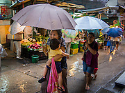 13 AUGUST 2013 - HONG KONG:  People shopping on Gage Street in Hong Kong use umbrellas to protect themselves from the rains of Typhoon Utor. Typhoon Utor (known in the Philippines as Typhoon Labuyo) is an active tropical cyclone located over the South China Sea. The eleventh named storm and second typhoon of the 2013 typhoon season, Utor formed from a tropical depression on August 8. The depression was upgraded to Tropical Storm Utor the following day, and to typhoon intensity just a few hours afterwards. The Philippines, which bore the brunt of the storm, reported 1 dead in a mudslide and 23 fishermen missing at sea. The storm brushed by Hong Kong bringing several millimeters of rain and moderate winds to the island but causing no reported damage or injuries. It is expected to make landfall in China.  PHOTO BY JACK KURTZ