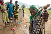 A girl balances buckets of water on both ends of a stick as prepares to carry them back home from a UNICEF-sponsored pump in the village of Game, Guera province, Chad on Tuesday October 16, 2012.