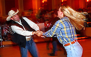 """09 DECEMBER 2002 - LAS VEGAS, NEVADA, USA: Justin Bond, from Colorado Springs, CO, dances with Crystal Sloyer, from Lake Forest, CA, in a bar at the Gold Coast Casino, Dec. 9, 2002, during the National Finals Rodeo. The NFR is the """"Super Bowl"""" rodeo; hundreds of thousands of rodeo fans come to Las Vegas for 10 days every December to participate, in one way or another, in the NFR. The Gold Coast hosts a number of NFR related events, including trophy presentations and free dances, during the NFR and many spectators and contestants come to the Gold Coast to watch television feeds of the rodeo and gamble. PHOTO BY JACK KURTZ"""