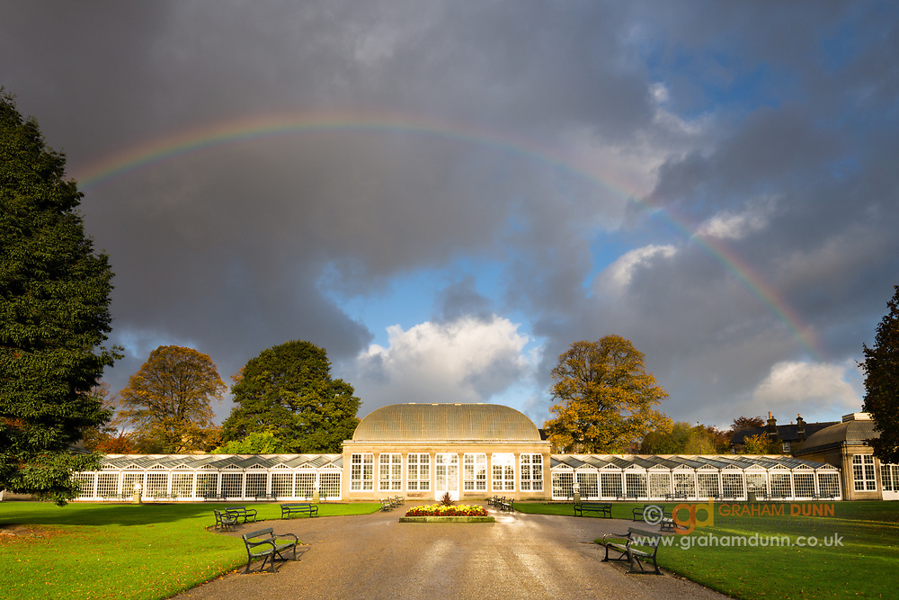 A rainbow arches over the Glass Pavillions in Sheffield's Botanical Gardens. Dramatic storm light in South Yorkshire, England, UK. An autumnal urban landscape.