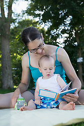 Mother and baby boy looking at a picture book in lawn, Munich, Bavaria, Germany