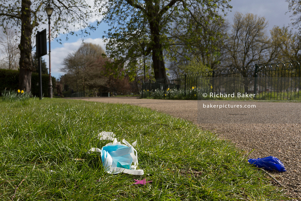 At the beginning of the second week of the UK's Coronavirus lockdown and in accordance with government guidelines for social distancing and local daily exercise, a used discaded surgical mask and glove lies in the grass alongside a path used by passing Londoners in Ruskin Park, a green public space in the borough of Lambeth, south London, on 30th March 2020, in London.