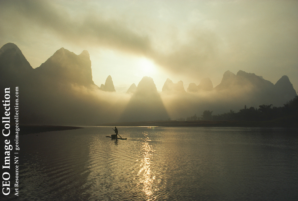 A man in a small boat in morning mist shrouding karst hills.