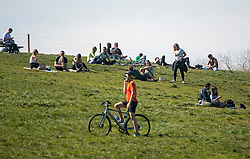 © Licensed to London News Pictures. 05/04/2020. London, UK. People sit in the sunshine at Hampstead Heath, London, which is prohibited during a lockdown for pandemic outbreak of the Coronavirus COVID-19 disease. The public have been told they can only leave their homes when absolutely essential, in an attempt to fight the spread of coronavirus COVID-19 disease. Photo credit: London News Pictures.