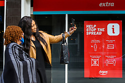 © Licensed to London News Pictures. 11/10/2020. London, UK. Women not observing social distancing take a selfie in front of 'Help Stop The Spread' poster in Wood Green, north London as another national coronavirus lockdown looms. <br /> SADIQ KHAN, Mayor of London has warned that a London lockdown cannot be ruled out as coronavirus cases in the capital soar. In a statement to MPs on Monday, 12 Oct 2020, Prime Minister Boris Johnson is expected to announce tougher local restrictions, outlining plans for a three-tier system, where each region in England is placed into a tier based on the severity of cases in the area. Photo credit: Dinendra Haria/LNP