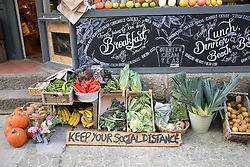 'Keep your social distance' sign outside greengrocer / deli, St Ives, Cornwall UK Oct 2020