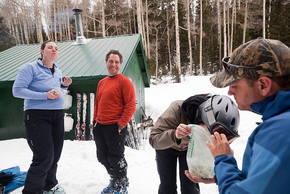 Meaghan Daly eats from Sterling Roop's bag of trail mix as Emily Miller and Judd MacRae look on outside the backcountry North Pole Hut, San Juan Mountains, Colorado.