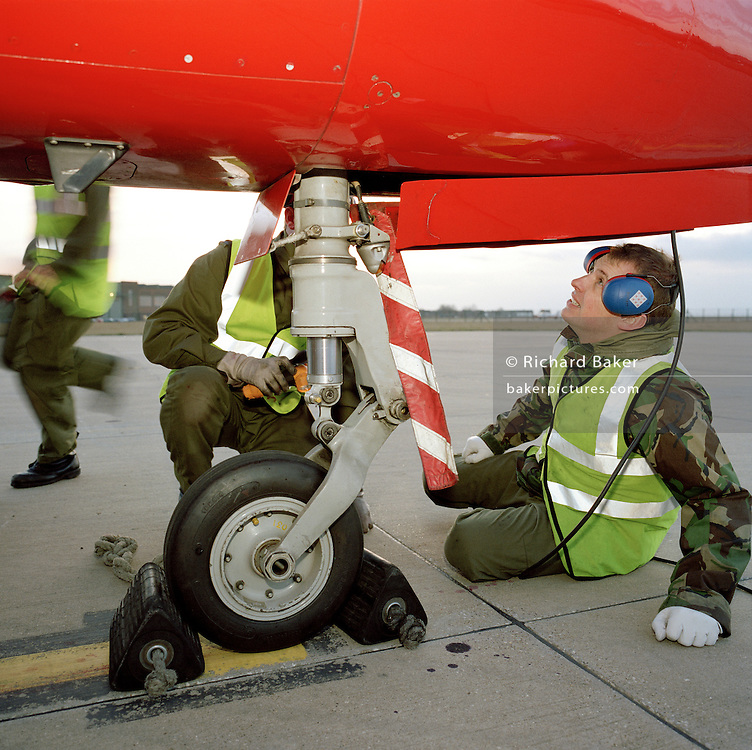 Engineering ground staff of the Red Arrows, Britain's RAF aerobatic team, makes repairs to a BAE Systems Hawk nosewheel.