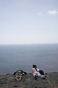 Peering over edge of sheer cliffs Dún Aengus fort Inishmore, Aran Islands, County Clare, Ireland