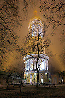 Bell tower of Kyiv-Pechersk Lavra at night. Contrasting trees'  silhouettes create frame around the bell tower highlighted by the beams from both sides in the foggy air. Winter, 2015.<br /> <br /> Вечерний снимок главной колокольни Киево-Печерской Лавры.