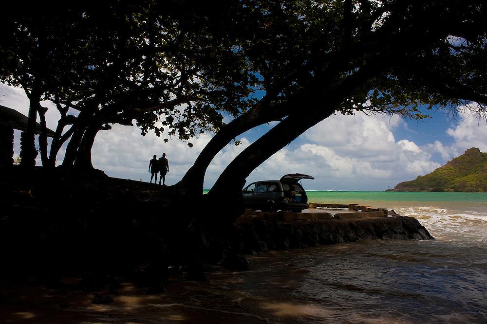 Couple silhouetted overlooking ocean at Kahana Bay, Oahu, Hawaii