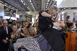 Former French Economy Minister and founder of political mouvement 'En marche!' Emmanuel Macron gets a shave during his visit to the Mondial Coiffure Beaute 2016 International Hair and Beauty Fair in Paris, France on September 12, 2016. Photo by Eliot Blondet/ABACAPRESS.COM