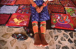 Local Panamanian woman in Portobelo displaying colorful handcrafted textiles called molas.