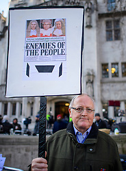 © Licensed to London News Pictures. 05/12/2016. London, UK. A Pro Brexit supporter holds up a banner showing a copy of a newspaper article, outside the Supreme Court  in Westminster, London on the first day of a  Supreme Court hearing to appeal against a November 3 High Court ruling that Article 50 cannot be triggered without a vote in Parliament. Photo credit: Ben Cawthra/LNP