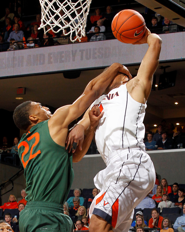Virginia guard Justin Anderson (1) is fouled by Miami forward Donnavan Kirk (22) during an NCAA basketball game Saturday Feb, 24, 2014 in Charlottesville, VA. Virginia defeated Miami 65-40.