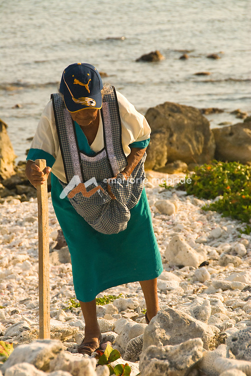 Mexican woman with walking stick along the beach on the Riviera Maya on the Caribbean coast in Akumal, Mexico.