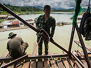16 SEPTEMBER 2014 - SANGKHLA BURI, KANCHANABURI, THAILAND: Thai soldiers working on the Mon Bridge repair job. The 2800 foot long (850 meters) Saphan Mon (Mon Bridge) spans the Song Kalia River. It is reportedly second longest wooden bridge in the world. The bridge was severely damaged during heavy rainfall in July 2013 when its 230 foot middle section  (70 meters) collapsed during flooding. Officially known as Uttamanusorn Bridge, the bridge has been used by people in Sangkhla Buri (also known as Sangkhlaburi) for 20 years. The bridge was was conceived by Luang Pho Uttama, the late abbot of of Wat Wang Wiwekaram, and was built by hand by Mon refugees from Myanmar (then Burma). The wooden bridge is one of the leading tourist attractions in Kanchanaburi province. The loss of the bridge has hurt the economy of the Mon community opposite Sangkhla Buri. The repair has taken far longer than expected. Thai Prime Minister General Prayuth Chan-ocha ordered an engineer unit of the Royal Thai Army to help the local Mon population repair the bridge. Local people said they hope the bridge is repaired by the end November, which is when the tourist season starts.    PHOTO BY JACK KURTZ