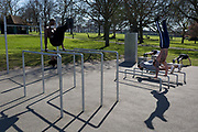 After a weekend of large numbers of Britons leaving London for holiday resorts and coastal beauty spots, and crowding into the capitals parks, the UK government is considering further restrictions of movement in public places to help social distancing during the Coronavirus pandemic. Indoor gyms are now closed but this open-air space in Ruskin Park, south London has attracted south Londoners including members of the Brixton Street Gym who exercise together in warm spring sunshine, on 23rd March 2020, in London, England.