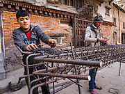 05 MARCH 2017 - KATHMANDU, NEPAL: Workers shape rebar into forms for cement columns in front of a building damaged in the 2015 earthquake. Much of Kathmandu is now a construction site because of rebuilding  two years after the earthquake of 25 April 2015 that devastated Nepal. In some villages in the Kathmandu valley workers are working by hand to remove ruble and dig out destroyed buildings. About 9,000 people were killed and another 22,000 injured by the earthquake. The epicenter of the earthquake was east of the Gorka district.     PHOTO BY JACK KURTZ