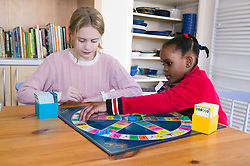 Two girls sitting at a table playing a game of Trivia Pursuit,