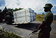 A Guyanese Defense Force soldier stands guard as a U.S. Air Force Airman ports nine aluminimum caskets with the remains of the followers of Rev. Jim Jones, leader of the People's Temple cult