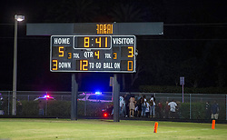 August 18, 2018 - Wellington, Florida, U.S. - A group gathers around one of the victims of a shooting at Palm Beach Central High School. Two adults were shot Friday night at a football game between Palm Beach Central and William T. Dwyer high schools, authorities said. The gunfire sent players and fans screaming and stampeding in panic during the fourth quarter of the game at Palm Beach Central High School in Wellington, Florida on August 17, 2018. (Credit Image: © Allen Eyestone/The Palm Beach Post via ZUMA Wire)
