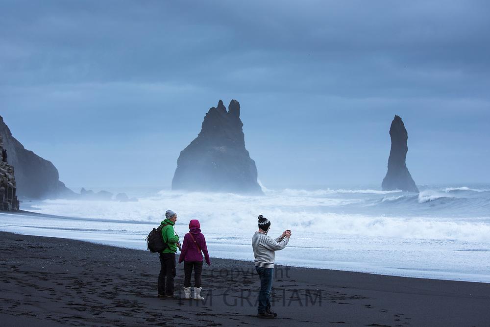 Tourist at Reynisdrangar basalt sea stacks (troll rocks) and black volcanic sand beach Reynisfjara near Vík i Myrdal, South Iceland