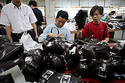 30 March 2006 - Dongguan, Guangdong Province - Factory workers inspect and pack new handbags for export.
