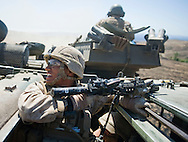LCpL. Alfredo Arroyo holds on while riding in an Assault Amphibious Vehicle during live-fire exercises for the 2nd Battalion, 5th Marine Regiment at Camp Pendleton.