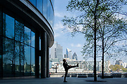 Young man exercising, with the City of London in the background while London is on lockdown as a result of the Coronavirus Pandemic on 16th April 2020 in London, United Kingdom. Coronavirus or Covid-19 is a new respiratory illness that has not previously been seen in humans. Much of Europe has been placed into lockdown, with stringent rules in place as part of a long term strategy, and in particular social distancing, and a stay at home policy.