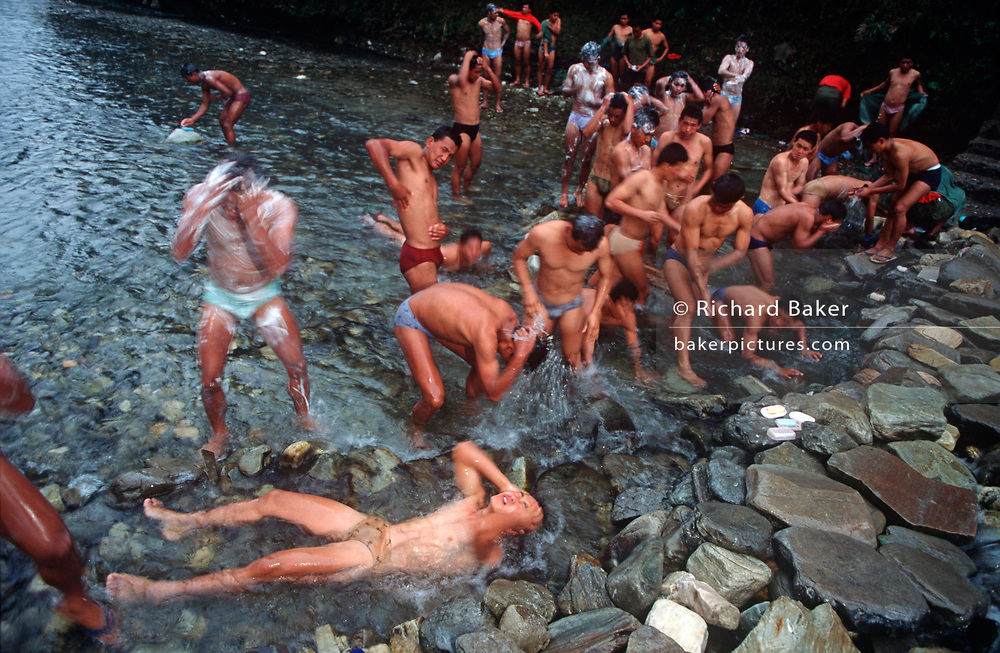 For their daily river washing ritual, young Nepali boys bathe in the river Seti Gandaki in a valley side near the British Gurkha Regiment's army camp at Pokhara during their recruitment selection held ever year, 16th January 1997, in Pokhara, Nepal. <br /> After a gruelling series of physical tests to eliminate the weaker and less able candidates. 60,000 boys aged between 17-22 (or 25 for those educated enough to become clerks or communications specialists) report to designated recruiting stations in the hills each November, most living from altitudes ranging from 4,000-12,000 feet. After initial selection, 7,000 are accepted for further tests from which 700 are sent down here to Pokhara in the shadow of the Himalayas. Only 160 of the best boys succeed in the journey to the UK. The Gurkhas have been supplying youth for the British army since the Indian Mutiny of 1857.  (Photo by Richard Baker / In Pictures via Getty Images)
