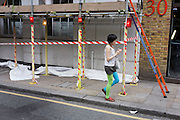 A female pedestrian wearing odd-coloured tights walks beneath construction site scaffolding and tape.
