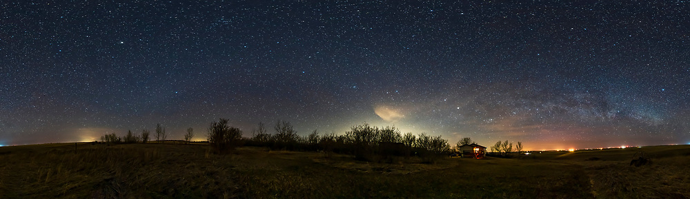 A 360° panorama of the northern spring sky taken from home on a very clear night April 20, 2020. <br /> <br /> The Milky Way is as low as it gets from my latitude of 51° North and appears here as a low arc across the northern horizon at right. To the south at left the faint glow of Gegenschein is visible in Virgo around the star Spica. There is the suggestion of the even fainter Zodiacal Band stretching across the south over to the western sky at centre brightened by light pollution and with a few annoying clouds over the urban areas to the west. <br /> <br /> Gemini, Cancer and Leo are at centre; Auriga and Perseus are right of centre. Arcturus is the bright star at upper left, Vega is the bright star at far right. <br /> <br /> This is a stitch of 8 segments each untracked for 30 seconds at f/2.8 with the Rokinon 12mm full-frame fish-eye lens in portrait orientation, and Nikon D750 at ISO 3200. I used LENR in-camera dark frame subtraction to reduce shadow noise and discolouration. — images shot without LENR had a lot of magenta cast in the shadows. Stitched with PTGui and assembled with the equirectangular projection. Topaz DeNoise AI applied to the ground, Noiseless CK from SkyLum/Luminar applied to the sky.