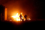 People run while a vehicle burns during riots at Hal Far Open Centre migrant camp in Hal Far, Malta, October 21, 2019. REUTERS/Darrin Zammit Lupi     TPX IMAGES OF THE DAY - RC1DCEEF5EA0