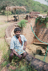 Indian man affected by polio; president of selfhelp group supported by charity ADD India; using oil pump to draw water from well to irrigate ground nut and paddy fields,